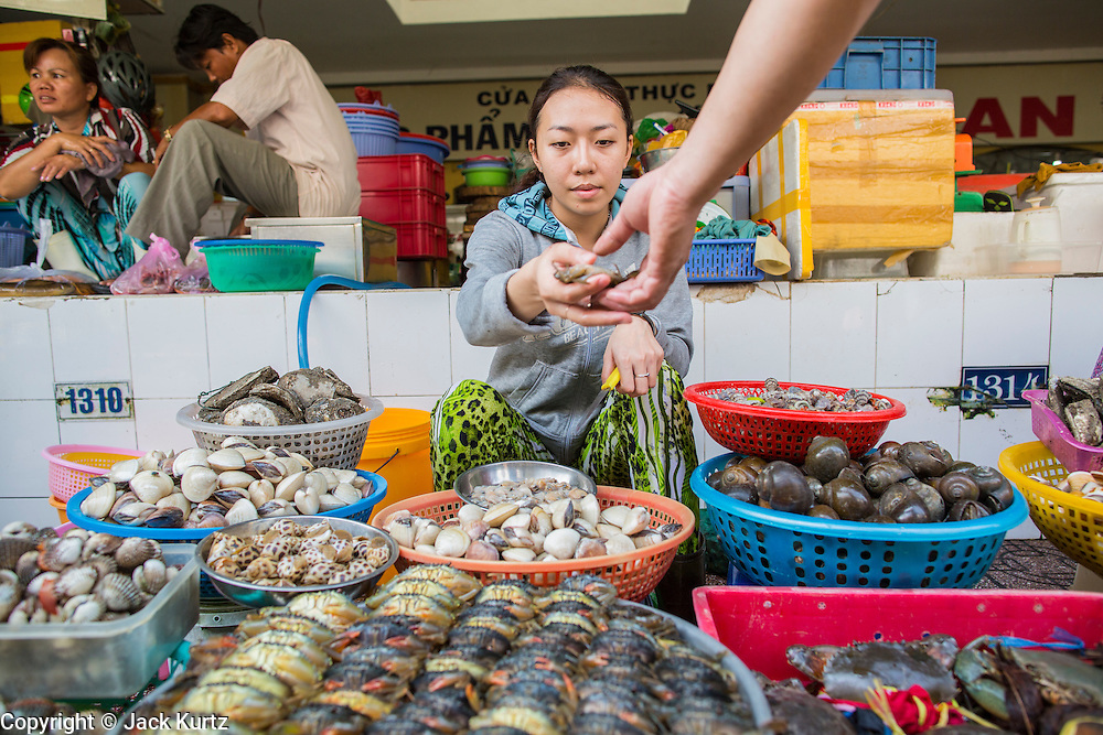 28 MARCH 2012 - HO CHI MINH CITY, VIETNAM:  A crab vendor sells a crab in the Ben Thanh Market in Ho Chi Minh City, Vietnam. Ben Thanh Market is a large market in the downtown area of Ho Chi Minh City (Saigon), Vietnam in District 1. The market is one of the earliest surviving structures in Saigon and one of the city's landmarks, popular with tourists seeking local handicrafts, textiles,ao dais (Vietnamese traditional dresses), and souvenirs, as well as local cuisine. The market developed from informal markets created by early 17th century street vendors gathering together near the Saigon River. The market was formally established by the French colonial powers in 1859. This market was destroyed by fire in 1870 and rebuilt to become Saigon's largest market. In 1912 the market was moved to a new building and called the New Ben Thanh Market to distinguish over its predecessor. The building was renovated in 1985.      PHOTO BY JACK KURTZ