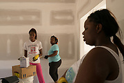 """BIRMINGHAM, AL – JULY 10, 2015: A family works on a home with Habitat for Humanity volunteers. <br /> <br /> In April 1998, a deadly F5 tornado ripped through the suburbs of Birmingham, Alabama, killing 32 people and destroying hundreds of homes. Seventeen years later, Matthew Seals is still learning to cope with the loss of his youngest son, who was killed in the storm. With help from Habitat for Humanity, Seals completed construction on a new home in 2015, where he continues to raise his remaining children and his new life as a paraplegic. Despite his own suffering from the tragedy, Seals volunteers with Habitat to help other families find their own form of stability through home ownership. """"Habitat gives you an opportunity to help yourself,"""" Seals said. """"Not just for the immediate need, but for the long term to become more self-sufficient, more self-confident, and more self-reliant."""""""