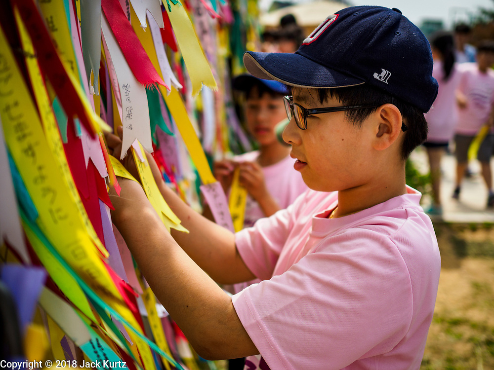 09 JUNE 2018 - IMJINGAK, PAJU, SOUTH KOREA:  South Korean school children hang prayer flags on a fence near the northernmost point on the South Korean side of the Korean DMZ in Imjingak. Imjingak is a park and greenspace in South Korea that is farthest north most people can go without military authorization. The park is on the south bank of Imjin River, which separates South Korea from North Korea and is close the industrial park in Kaesong, North Korea that South and North Korea have jointly operated.    PHOTO BY JACK KURTZ