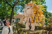 A visitor enjoys the floral lions which are part of the Chelsea Fringe and the Chelsea in Bloom Floral Safari in Duke of Yorks Square, on the Kings Road. They were created by All For Love, London.