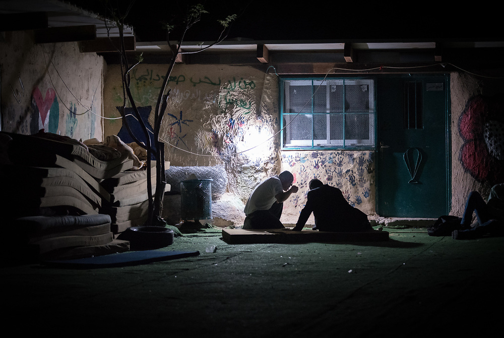 3 October 2018, Jerusalem, Occupied Palestinian Territories: Two men share a simple night meal outside the school building in Khan al Ahmar. Khan al Ahmar is a Bedouin community located within the East Jerusalem Periphery, in E1 area. It is home to 32 families, 173 persons in total, including 92 children and youths. The community has a mosque and a school, which was built in 2009 and serves more than 150 children between the ages of six and fifteen, from Khan al Ahmar and other nearby communities. With due date 1 October 2018, Israeli authorities threaten to demolish the site, thereby making room for nearby Israeli settlements to expand.