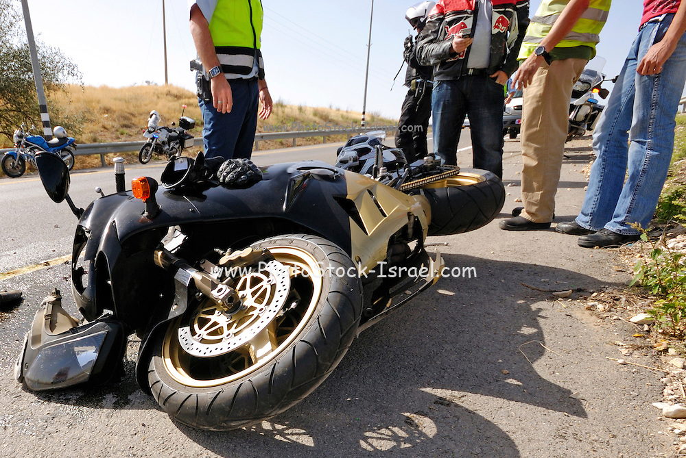 Israel, A motorbike lies on the road after a traffic collision injured person (not in view) is treated by medics