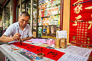 """22 JANUARY 2013 - BANGKOK, THAILAND:  A calligrapher works on Chinese New Year for customers at his table on Charoen Krung Road in Bangkok's Chinatown district. Chinese New Year is not an official public holiday in Thailand, but it is one the biggest celebrations in the Bangkok, which has a large Chinese population. Chinese New Year is February 10 this year. It will be the """"Year of the Snake.""""     PHOTO BY JACK KURTZ"""