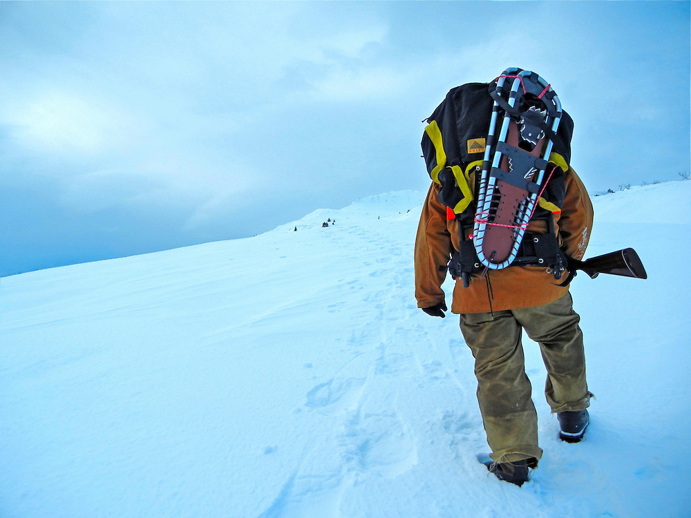 A hunter climbs to the top of a snow covered mountain on Kodiak Island.