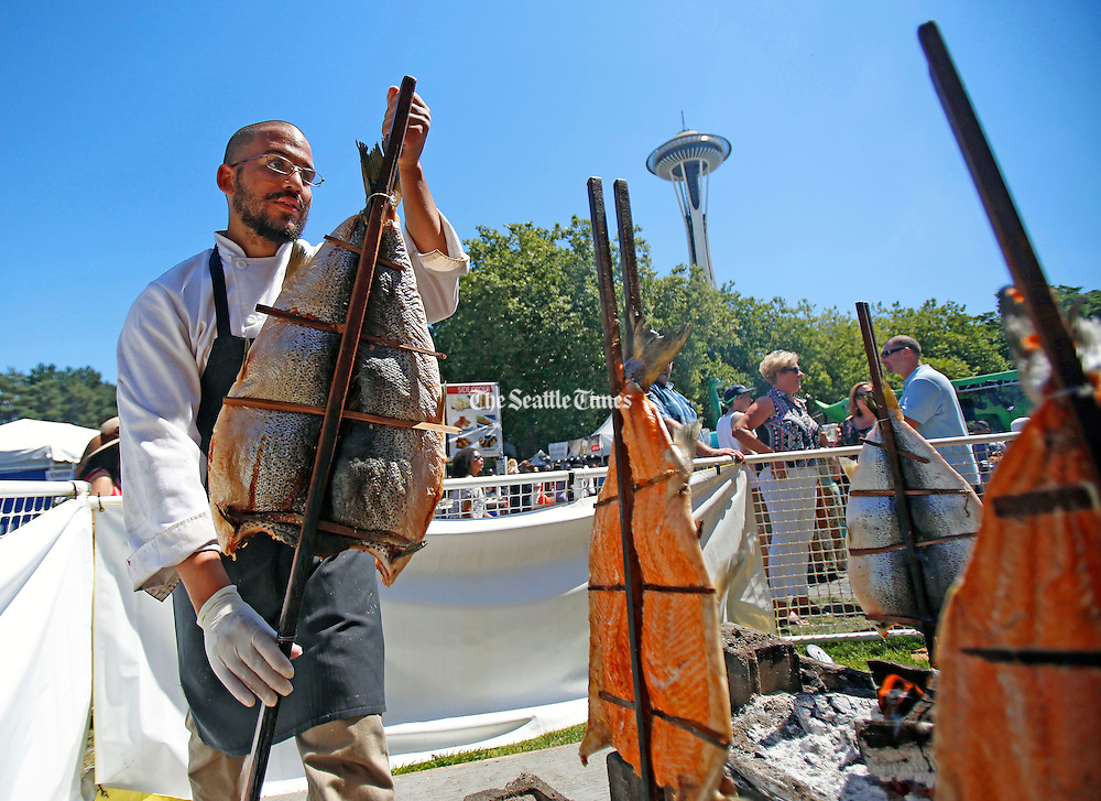Cook Jesus Gineste of Classic Catering carries a alder-smoked king salmon to be prepared during the Bite of Seattle at the Seattle Center, Sunday, July 19, 2015. <br /> <br /> Sy Bean / The Seattle Times