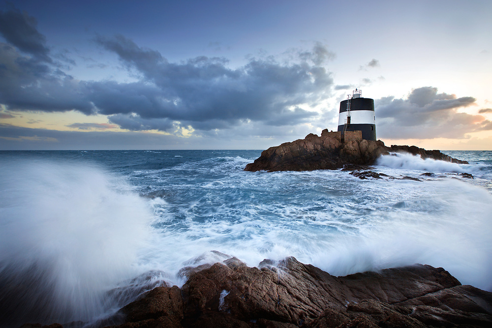 Rough sea and waves crashing over the rocks at Noirmont lighthouse in Jersey, Channel Islands