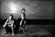 Two brothers stand together on the end of a pier at sunset after a long day of swimming.