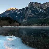 Ice covered Silver Lake reflects some sunset light from Hope Mountain in Silver Lake Provincial Park near Hope, British Columbia, Canada