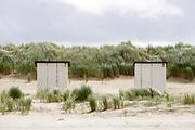 Nederland, Groede, 5-9-2019Strand met strandhuisjes en helmgras tegen de duinen in de wind..Foto: Flip Franssen