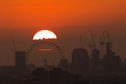 © Licensed to London News Pictures. 20/04/2018. London, UK. Sunset behind the London Eye in a hazy sky this evening following another hot day in the capital. London is currently experiencing hot, humid and hazy weather. Photo credit: Vickie Flores/LNP