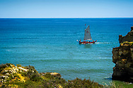 Sailboat full of people off the coast of Lagos, Portugal on a sunny, blue sky day.