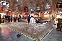 Iran, Tabriz, 23.08.2016: Teppichhändler auf dem Basar in Tabriz begutachten einen aussergewöhlich grossen (40 Quadratmeter) und schönen Teppich, Provinz Ost-Aserbaidschan, Nordwest-Iran.