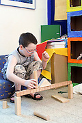 Young boy of 8 building with wooden building blocks in a playroom