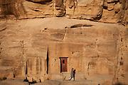 Bedouin man walking in front of a sandstone rockface with a door cut into it. Part of the Petra, Jordan complex.