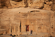 Bedouin man walking in front of a sandstone rockface with a door cut into it. Part of the Petra, Jordan complex.