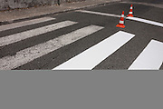 Two traffic cones prevent motorists driving over the half-finished paint job of fresh stripes on a zebra crossing, on 16th July, at Alcobaca, Portugal. (Photo by Richard Baker / In Pictures via Getty Images)