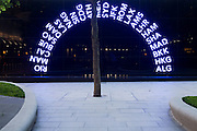 """The three letter IATA codes for some of the world's airport destinations have been used as part of an art design in a plaza outside Heathrow Airport's Terminal 5. An arc of these neon-lit codes form an arch on a panel near one of the 1,500 semi mature trees. Illuminated in a sequence, they are all lit here before the sequence re-starts and they all become dimmed. Terminal 5 was created by the Richard Rogers Partnership (now Rogers Stirk Harbour and Partners) and has the capacity to serve around 30 million passengers a year. From writer Alain de Botton's book project """"A Week at the Airport: A Heathrow Diary"""" (2009)."""