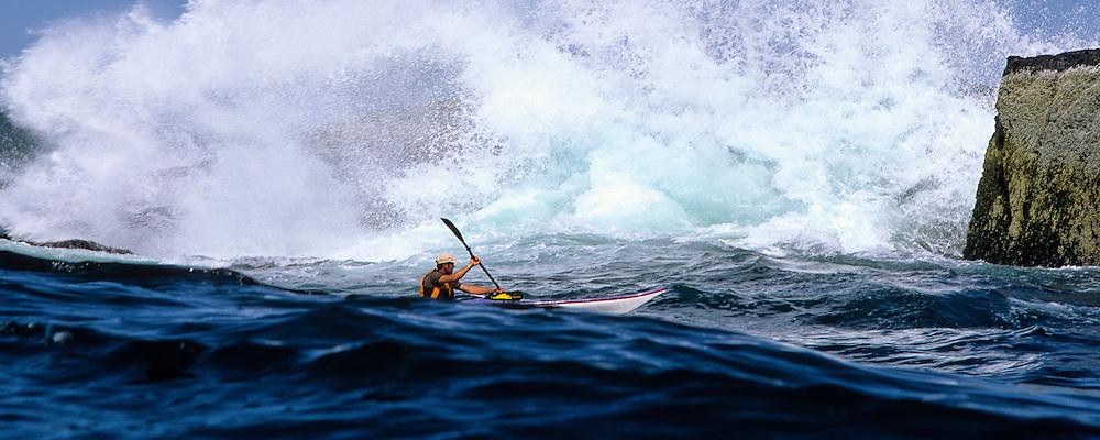 SEA KAYAKING, MAINE COAST, paddler Marc Bourgoin amid the spray from a tidal surge at Douglas Ledges, Naraguagas Bay