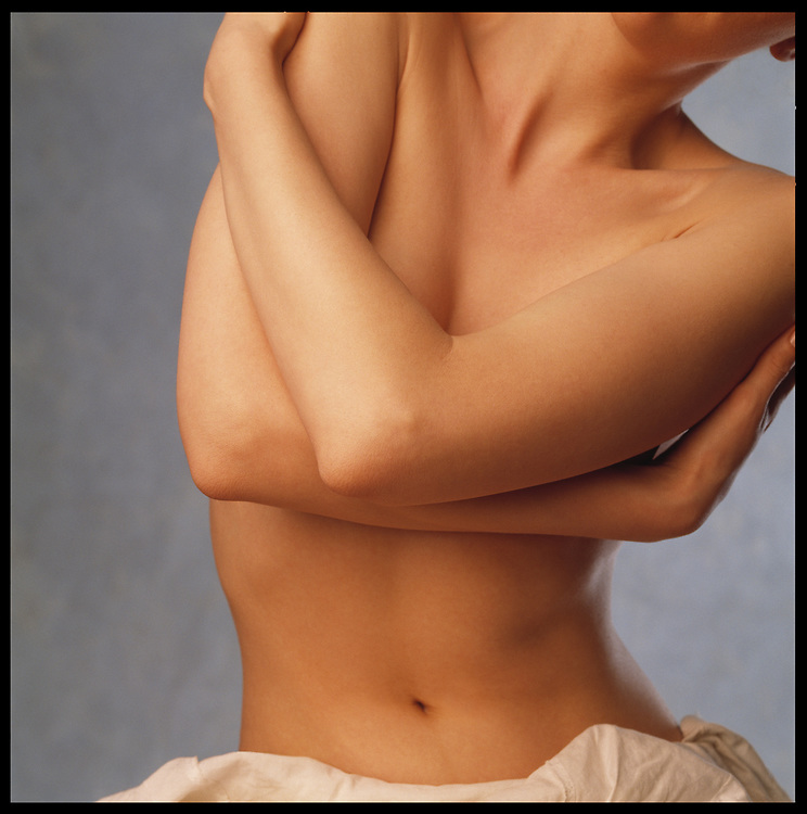 Skincare photo of nude woman's flawless body with arms crossed in front of chest