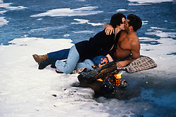 Sexy man without a shirt kissing a girl by a bonfire on a frozen lake