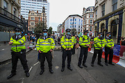 Police observe XR activists protesting near Covent Garden in central London on Monday, Aug 23, 2021. This is a two week planned of action against new fossil fuel investments. XR protestors are aiming to occupy parts of central London for two weeks from Monday, aiming to force the Government to halt all new investment in fossil fuels. (VX Photo/ Vudi Xhymshiti)
