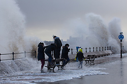 © Licensed to London News Pictures. 03/01/2014.New Brighton, UK . Pedestrians are caught out as waves hit New Brighton promenade, with the Liverpool skyline in the background.  Photo credit : Andrew Dawson/LNP