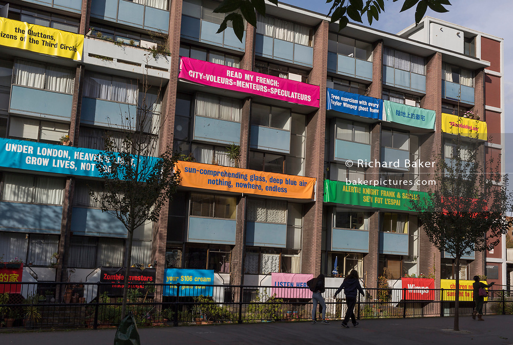 """Banners on the balconies of homes in Bowater House on the Golden Lane Estate to protest about the 10-storey luxury apartment development called The Denizen, a controversial building by Taylor Wimpey that locals say will dominate their view and block their daylight, on 30th October 2017, in London, England. Residents on the Estate have erected banners by artists Jeremy Deller and Elizabeth Price to picket the developers. Despite this, Wimpey say, """"We are one of the UK's largest residential developers. As a responsible developer we are committed to working with local people and communities."""""""