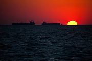 Solar power or oil? Oil tankers and fishing boat off Galveston, Texas, in the Gulf of Mexico, at sunset