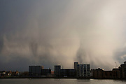 Rain pours down in the distance over the silhouette of riverside buildings in Bermondsey in London, UK.