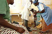 Kambou Sansan, 4, a malnourished boy, is weighed by medical staff during a visit at the Panzarani health center in the village of Panzarani, Zanzan region, Cote d'Ivoire on Friday November 25, 2011.