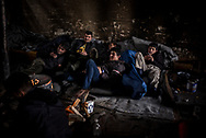 Migrants from Afghanistan are seen typing on their portable phones in an abandoned wearhouse in Belgrade, Serbia. March 19th, 2017. Federico Scoppa