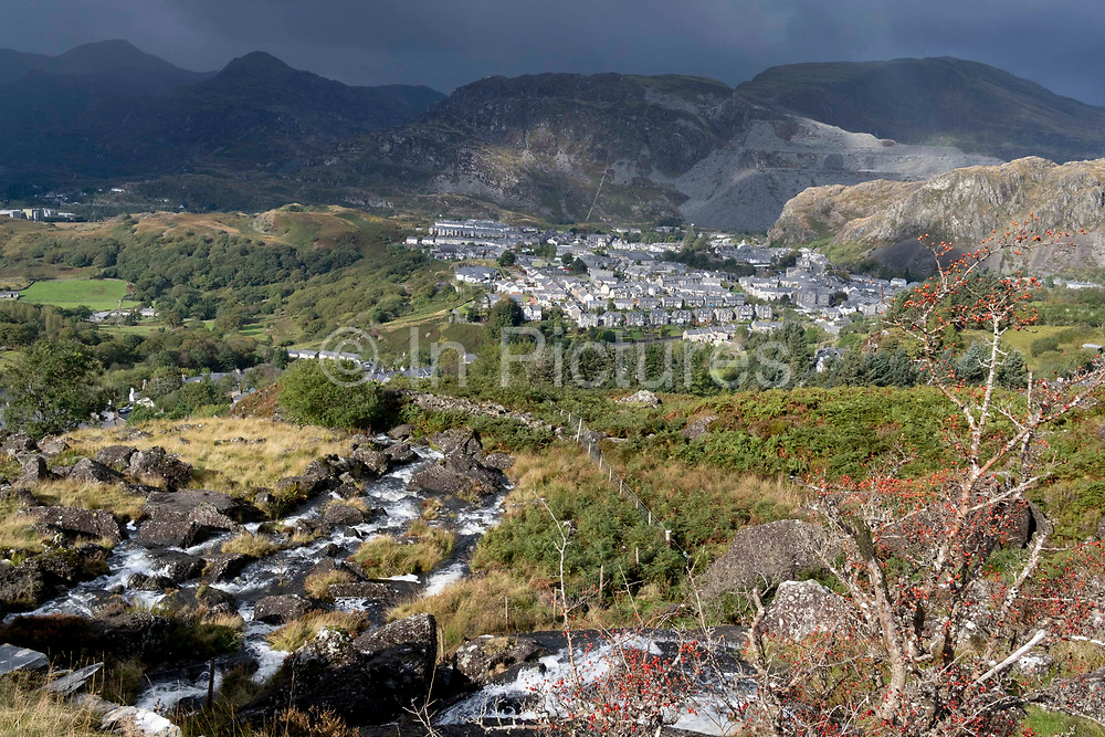 With slate mountains dominating above, an aerial view of houses in the industrial revolution-era town of Blaenau Ffestiniog, on 5th October 2021, in Blaenau Ffestiniog, Gwynedd, Wales. The derelict slate mines around Blaenau Ffestiniog in north Wales were awarded UNESCO World Heritage status in 2021. The industry's heyday was the 1890s when the Welsh slate industry employed approximately 17,000 workers, producing almost 500,000 tonnes of slate a year, around a third of all roofing slate used in the world in the late 19th century. Only 10% of slate was ever of good enough quality and the surrounding mountains now have slate waste and the ruined remains of machinery, workshops and shelters have changed the landscape for square miles.