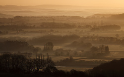 © Licensed to London News Pictures. 05/03/2014. Butser Hill, Hampshire, UK. A misty sunrise across the South Downs National Park, today 5th February 2014. Photo credit : Rob Arnold/LNP