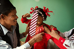 Kumari Dangol, 9, must wear red—the school tie being her only nod to convention. In other respects, she's like any other schoolchild, except that her teachers and fellow pupils address her as Dya Maiju—Little Girl Goddess.