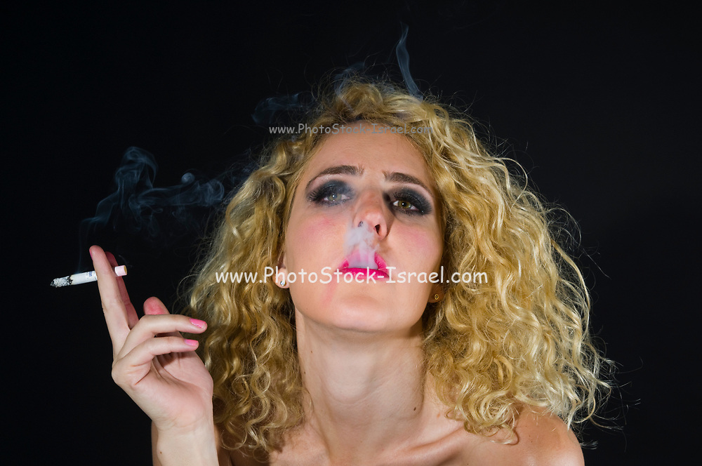 Young glamorous woman enjoys a cigarette