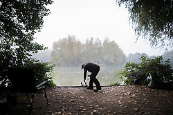 © Licensed to London News Pictures. 31/10/2016. Godalming, UK. A fisherman tends his rods in early morning fog on a lake near Godalming.  Photo credit: Peter Macdiarmid/LNP