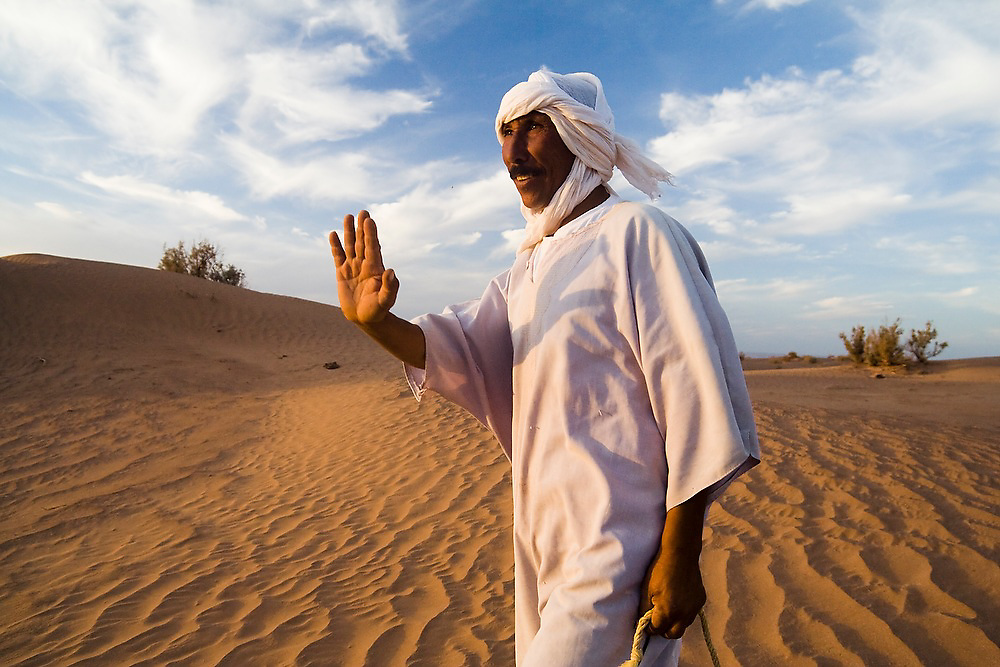 Camel guide Elhussein Sbiti raises his hand in greeting on a three-day camel trek to the remote sand dunes of Erg Zehar, near M'hamid in the Moroccan Sahara. Sbiti, like many berber nomads in the region, has found opportunity in the new tourism trade burgeoning since the settling of tensions between Morocco and neighboring Algeria..