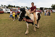 A teenage traveller adertises a pony at the ancient annual Priddy Sheep (and horse) fair in Somerset, England. The young man rides bareback around a field on the outskirts of the village. Set in the Mendip Hills, in the south-western English county of Somerset, the Priddy Sheep fair is host to an odd mix of farmers and travellers (commonly and incorrectly known as gypsies). In this field set aside purely for travellers, many with West Country accents but also with nearby Welsh and Irish too, deals are done with a traditional spit on the hand and a smacking of palms, selling a pony to another family. The Priddy Sheep Fair moved from the city of Wells in 1348 because of the Black Death.