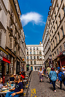 Tourists walk up the hill along Rue des Martyrs toward Montmartre, Paris, France.