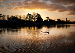 © Licensed to London News Pictures. 01/02/2018. London, UK. The sun rises over the Thames at Hampton Court. A Temperatures are set to drop to near freezing over the next few days. Photo credit: Peter Macdiarmid/LNP