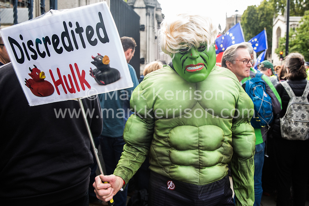 "London, UK. 25 September, 2019. A man dressed as the Incredible Hulk stands among pro- and anti-Brexit activists protesting outside the Houses of Parliament on the day after the Supreme Court ruled that the Prime Minister's decision to suspend parliament was ""unlawful, void and of no effect""."