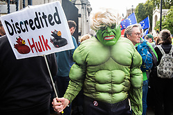"""London, UK. 25 September, 2019. A man dressed as the Incredible Hulk stands among pro- and anti-Brexit activists protesting outside the Houses of Parliament on the day after the Supreme Court ruled that the Prime Minister's decision to suspend parliament was """"unlawful, void and of no effect""""."""