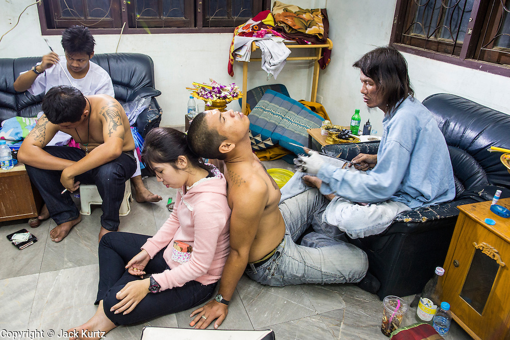 """22 MARCH 2013 - NAKHON CHAI SI, NAKHON PATHOM, THAILAND: Monks' living quarters are used as a tattooing room for sacred Sak Yant tattoos at Wat Bang Phra. Wat Bang Phra is the best known """"Sak Yant"""" tattoo temple in Thailand. It's located in Nakhon Pathom province, about 40 miles from Bangkok. The tattoos are given with hollow stainless steel needles and are thought to possess magical powers of protection. The tattoos, which are given by Buddhist monks, are popular with soldiers, policeman and gangsters, people who generally live in harm's way. The tattoo must be activated to remain powerful and the annual Wai Khru Ceremony (tattoo festival) at the temple draws thousands of devotees who come to the temple to activate or renew the tattoos. People go into trance like states and then assume the personality of their tattoo, so people with tiger tattoos assume the personality of a tiger, people with monkey tattoos take on the personality of a monkey and so on. In recent years the tattoo festival has become popular with tourists who make the trip to Nakorn Pathom province to see a side of """"exotic"""" Thailand. The 2013 tattoo festival was on March 23.    PHOTO BY JACK KURTZ"""