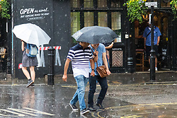 Soho, London, June 2nd 2017. Two men share an umbrella as one of the thunderstorms predicted by the Met Office passes over Old Compton Street in Soho, London.