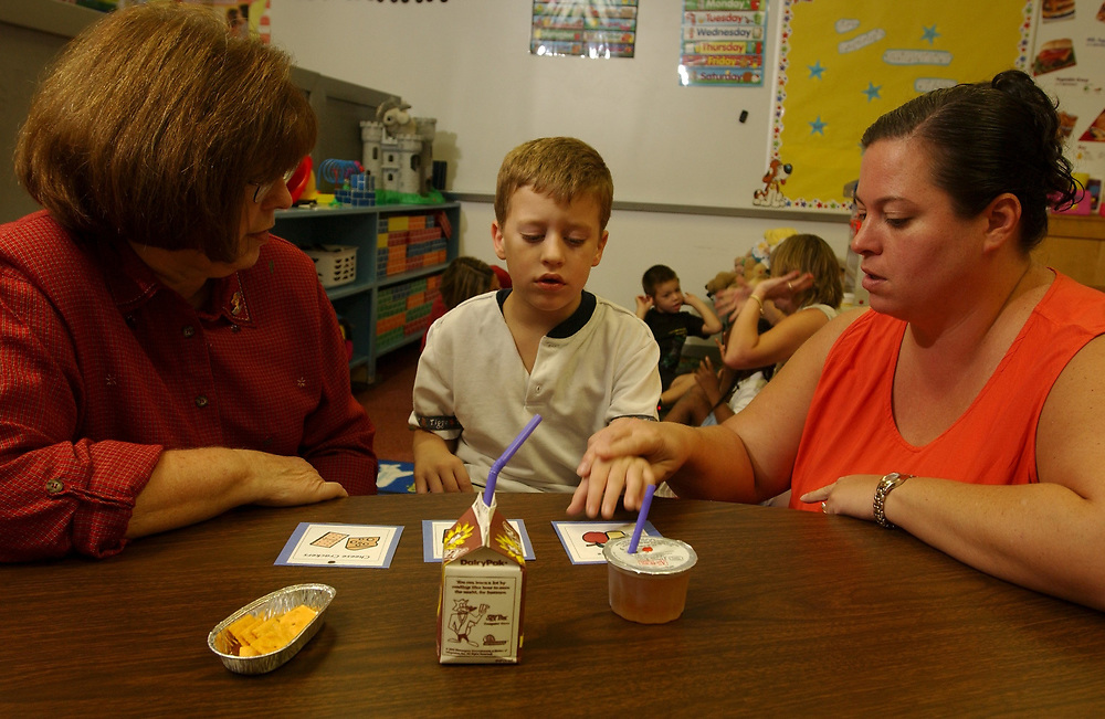 Gun Barrel City, Texas September 9, 2003:   Education at Lakeview and Southside Elementary Schools in the Mabank Independent School Discrict in northeast Texas. <br /> Autistic student (6 years old) being trained on Picture Exchange Communication System (PECS) where he gives a picture of what he wants to the teacher in order to receive the wanted item. MODEL RELEASE SP64 (student) SP66(teacher on right) SP69 (teacher on left). <br /> ©Bob Daemmrich