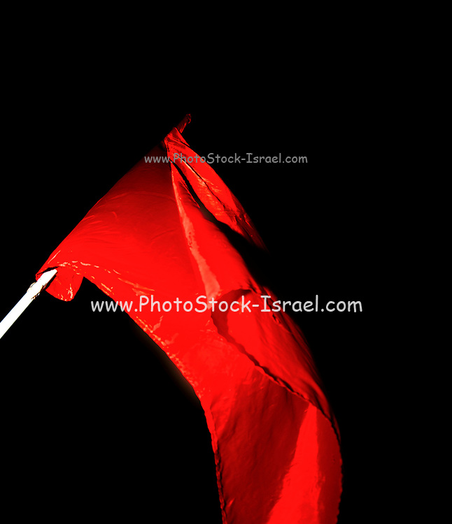 The red communist movement flag flying high during a protest on black background