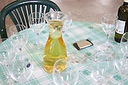 Tasting the wine at a table with a decanter with white wine and glasses. Kantina Miqesia or Medaur winery, Koplik. Albania, Balkan, Europe.