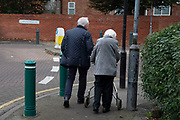 Street scene of an elderly couple making their way along the pavement together in Moseley / Kings Heath in Birmingham, United Kingdom.
