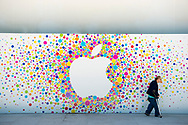 A senior adult using a crutch walks past the exterior of an Apple Store in Aix-en-Provence, France