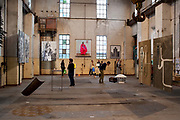 Visitors look at the artworks at an exhibition: Umspannzentrale in July 2013, the show was part of the Kunst-an-spreeknie festival. It was held in an old electricity transformer station, 78 Wilhelminenhofstraße, Schoneweide, Berlin, Germany.